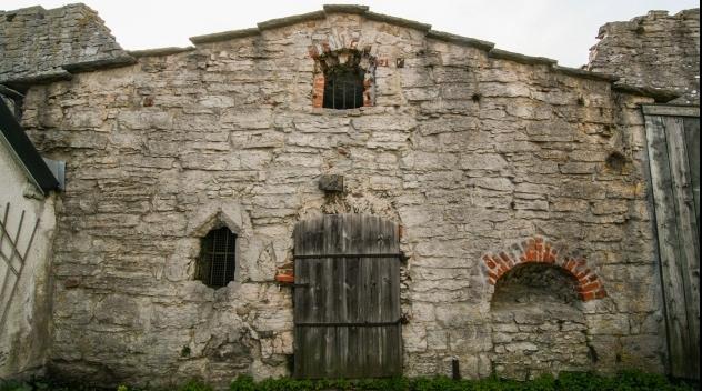 Fotografi på medeltida byggnad intill ringmuren i Visby.