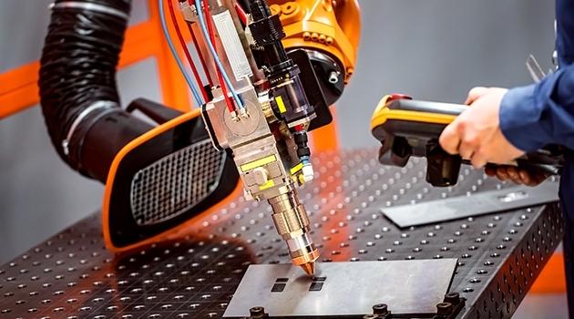 Fotografi på industrirobot som skär plåt med laser.