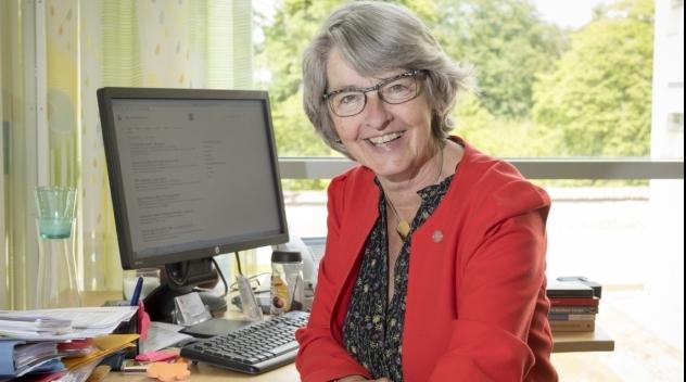 Fotografi av Elisabet Nihlfors stående vid sitt skrivbord.