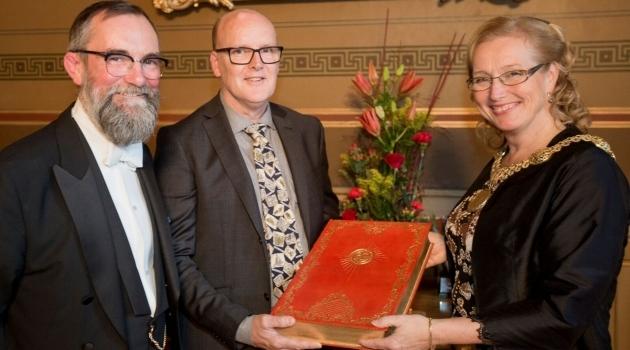 Den nya gästboken äverlämnas till rektor Eva Åkesson.