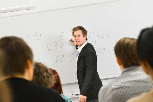 Fotografi från ett klassrum med lärare och whiteboard längst fram.
