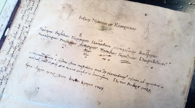Första bladet i en uppslagen bok, där man ser handskrivna rader på grekiska