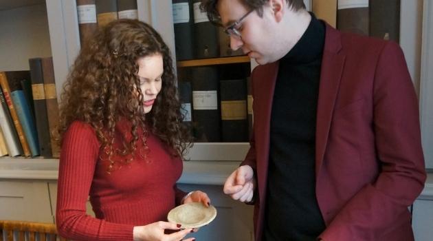 Fotografi med forskare som studerar en keramikskål med inskrifter.
