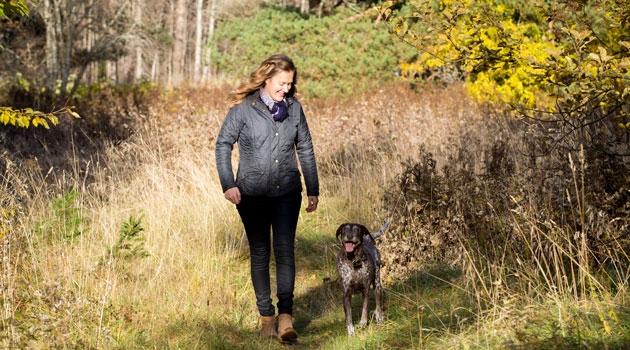 Tove Fall promenerar i skogen med sin hund