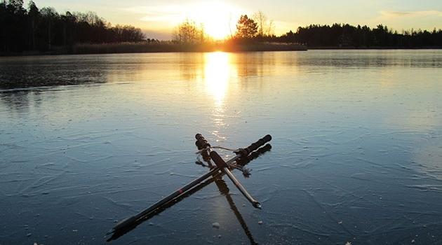 Ispik och isborr ligger på en frusen sjö.