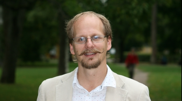 Personporträtt på Mattias Lundberg. Fotograferat utomhus i en park.