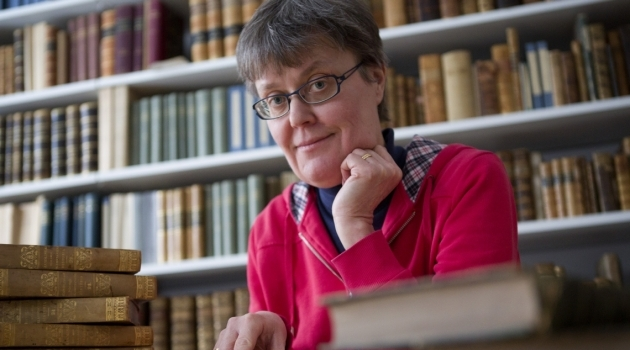 Fotografi på Maria Ågren vid ett skrivbord framför en bokhylla.
