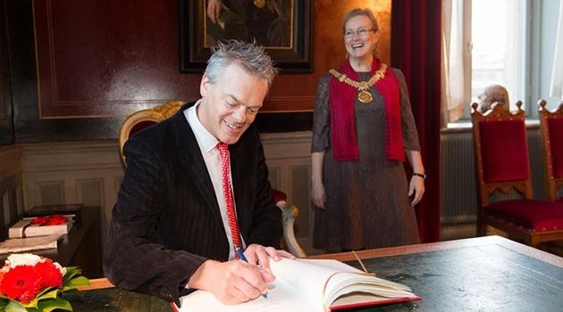 Edvard Moser signerar Uppsala universitets gästbok.