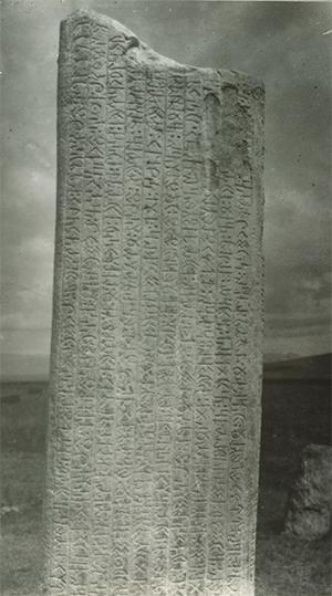 Fotografi på rest sten med inristade skrivtecken.