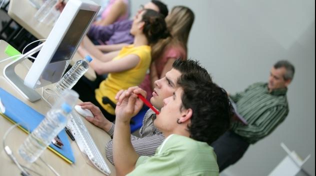 Fotografi på elever framför datorskärm.