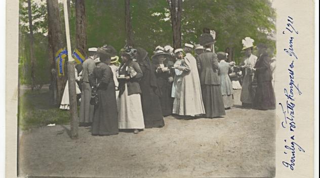 Ett stort sällskap kvinnor i kläder från sekelskiftet 1900 pratar med varandra