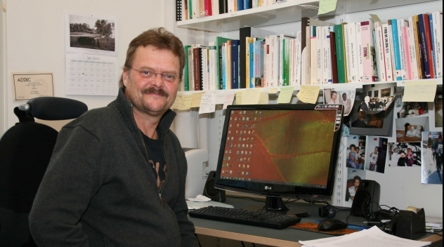Fotografi på Sten Hagberg framför datorn i hans tjänsterum.