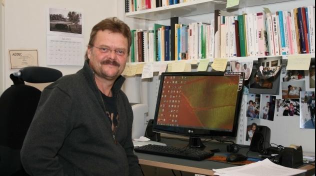 Fotografi på Sten Hagberg framför datorn i hans tjänsterum .