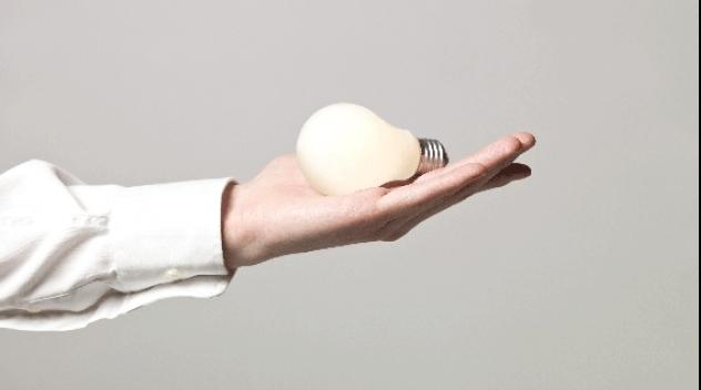 Fotografi på hand som håller glödlampa som lyser.