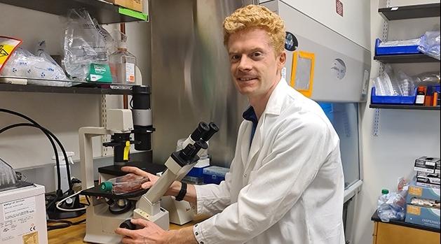 Jonathan Cedernaes i vit rock framför ett mikroskop i ett labb.