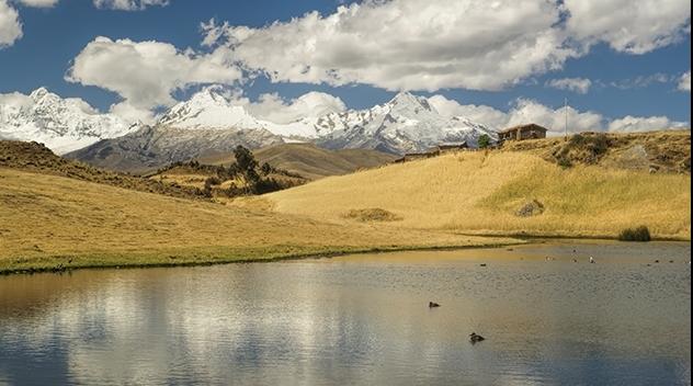 Landskapsfotografi med sjö i förgrunden och snötäckta berg i bakgrunden.