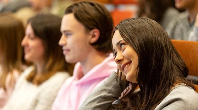 Tre studenter som lyssnar uppmärksamt