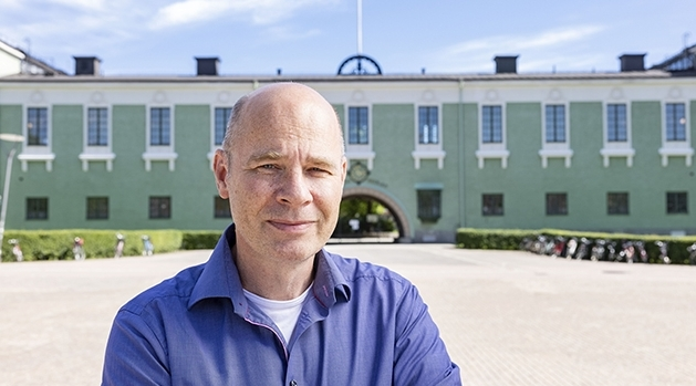 Göran Nygren, iförd blå skjorta, framför grön byggnad med vita fönsterkarmar.