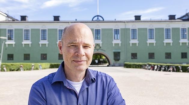 Göran Nygren, in a blue shirt, in front av a green building.