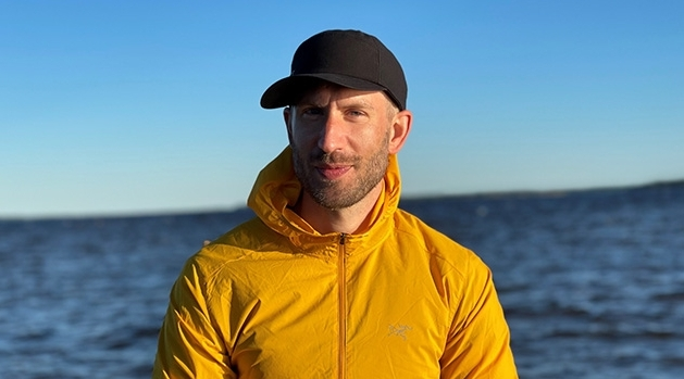 Alexander Rozental standing by the sea. He wears a yellow jacket and a black cap
