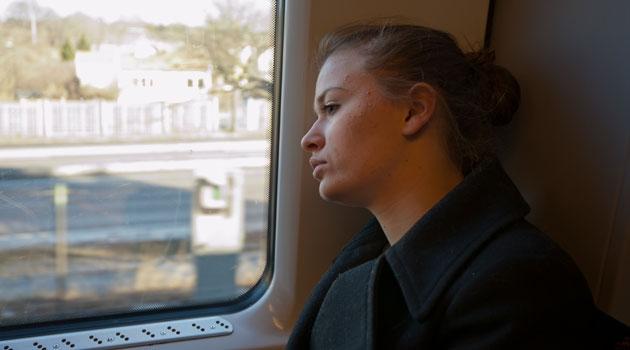 Kvinna sitter på ett tåg och tittar ut genom fönstret