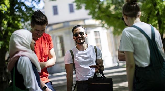 Studenter i Engelska parken sommartid som umgås och skrattar