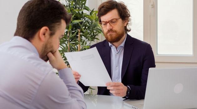 Två män sitter mittemot varandra vid ett bord.