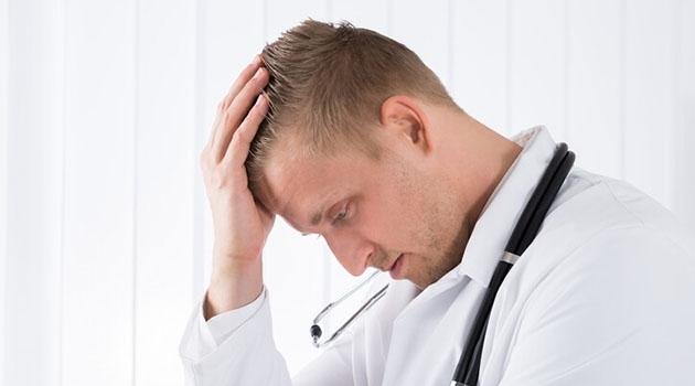 Man i vit rock med stetoskop runt halsen hänger med huvudet i handen.