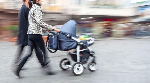 Ett par som går med barnvagn.
