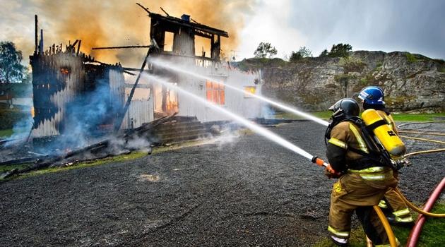 Brandmän som sprutar vatten på ett brinnande hus