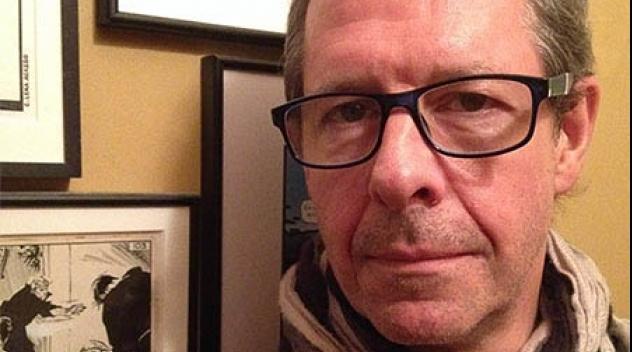 Porträtt av David Gedin fotograferat framför tavlor med serier.