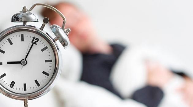 Bilden visar en man som sover med en väckarklocka i förgrunden.