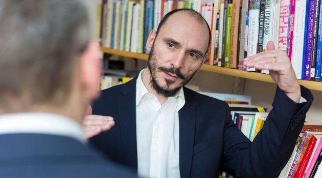Enrico Baraldi gesticulates in front of bookcase.