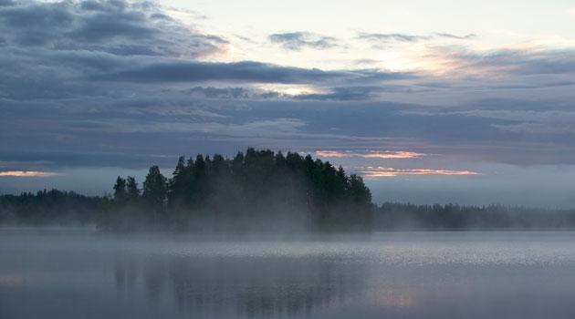 Solnedgång vid en sjö, med dimma över vattnet