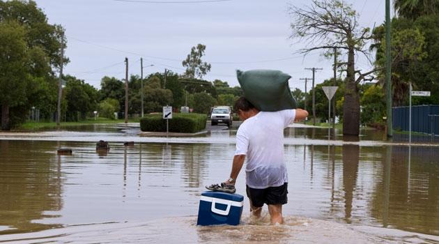 Man som flyr från sitt hem under en översvämning.