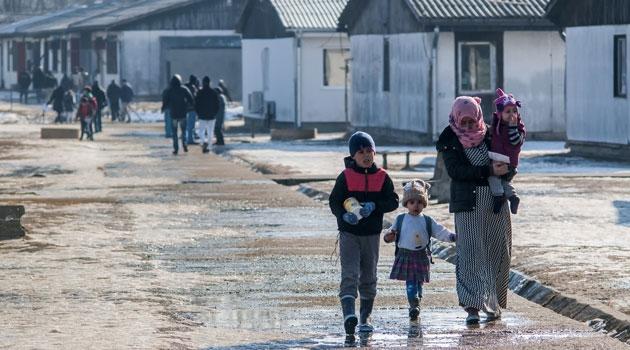 En mamma med tre barn kommer gående i ett flyktingläger