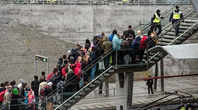 Flyktingar köar i en trappa upp från perrongen på en tågstation