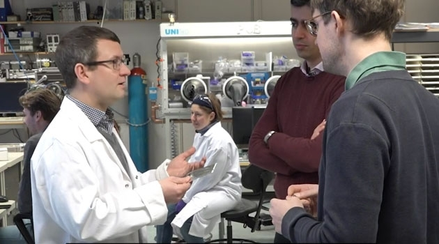Daniel Brandell talking to Reza Younesi och Erik Berg, in the laboratory.