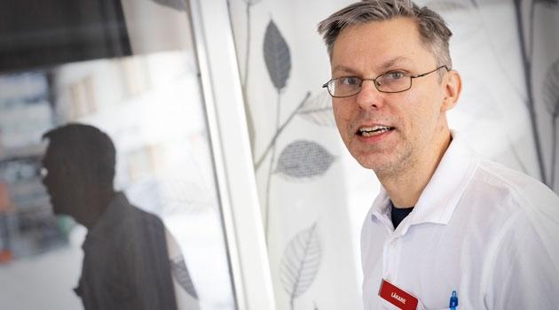 porträtt av Per-Ola Carlsson där man ser hans skugga i bakgrunden