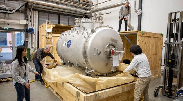 Några personer packar upp den enorma acceleratormodulen.