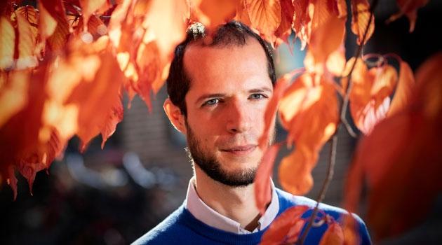 Porträtt av Gabriele Messori med röda höstlöv.