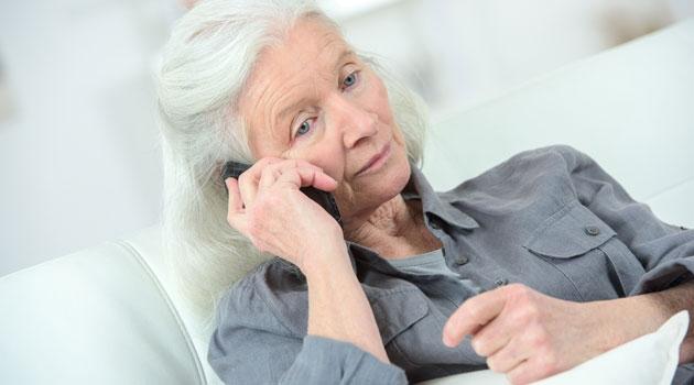 Äldre kvinna sitter i soffan och pratar i mobiltelefon.