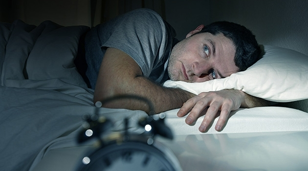Man lying in bed with his eyes open.