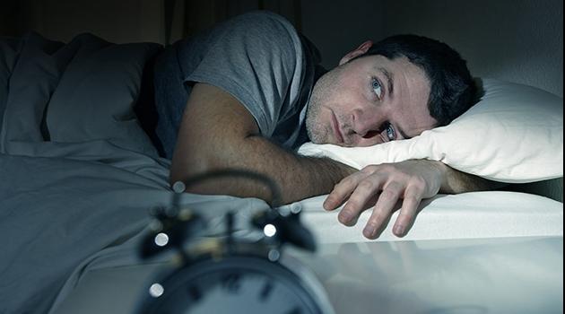 Man ligger i säng med öppna ögon.