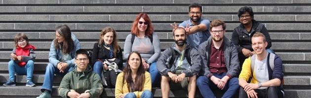 En grupp av människor sitter på en stentrappa.