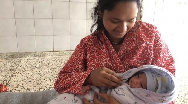 Kvinna med mörkt hår och rödblommig klädsel håller ett nyfött barn i famnen