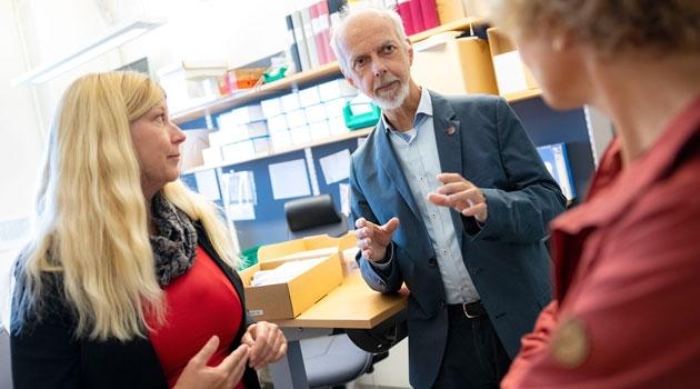 Inger och Ulf står och pratar i ett arbetsrum.