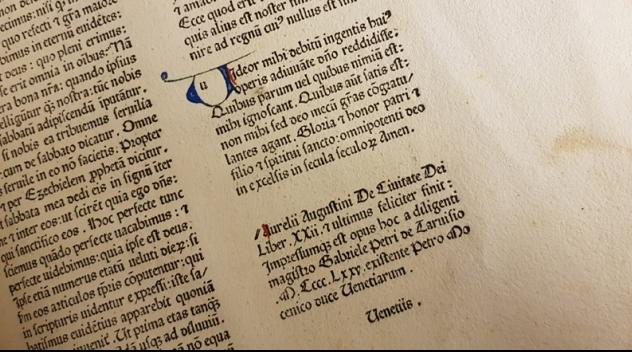 svart text mot vit botten, en initialt V målat i blått och rött