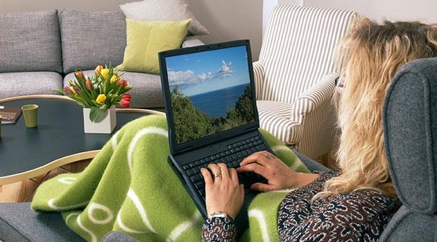 Kvinna sitter i en fåtölj med en dator i knät.