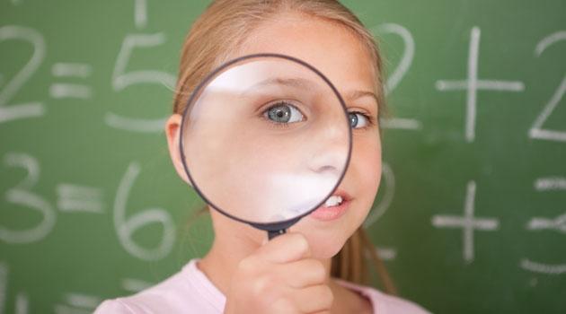 En flicka framför svarta tavlan som kikar genom ett förstoringsglas.